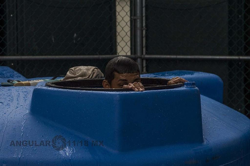 migrante bañandose en un tinaco en el campamento instalado en el Estadio Jesús Martínez Palillo, de la Ciudad Deportiva