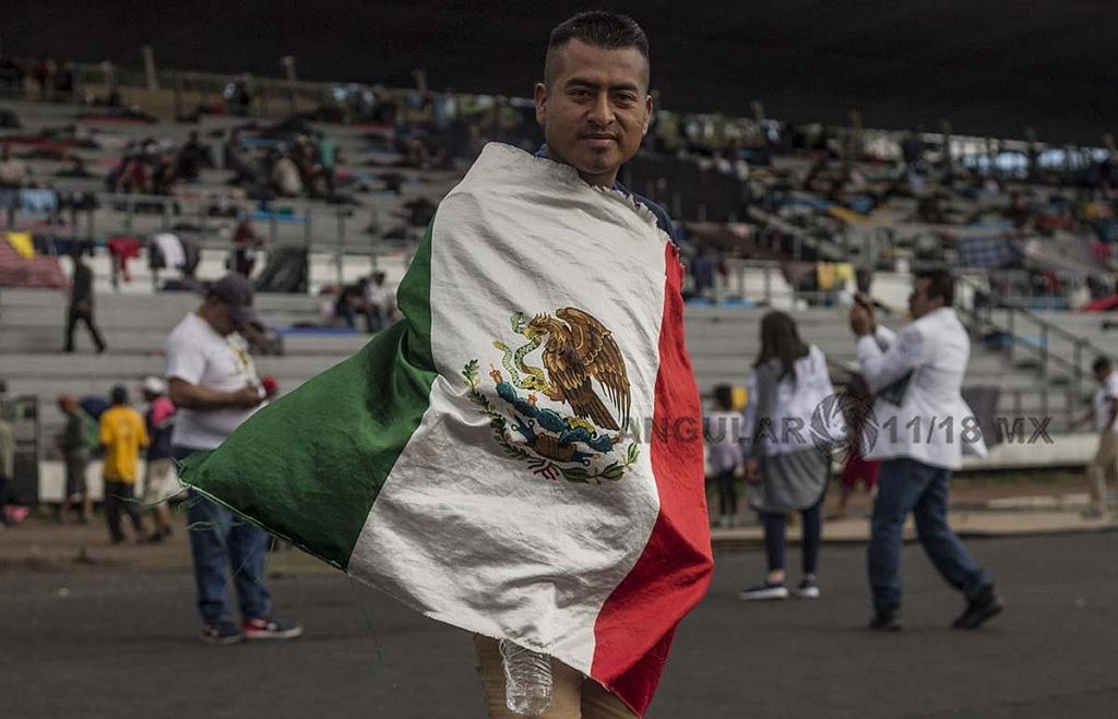 migrante con la bandera de México en el Estadio Jesús Martínez Palillo, de la Ciudad Deportiva