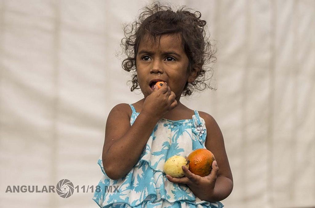 niña migrante comiendo fruta en el campamento instalado en el Estadio Jesús Martínez Palillo, de la Ciudad Deportiva
