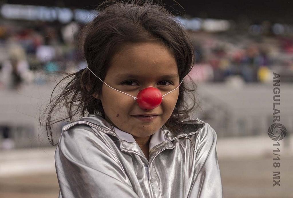 niña migrante con una nariz de payaso en el campamento instalado en el Estadio Jesús Martínez Palillo, de la Ciudad Deportiva