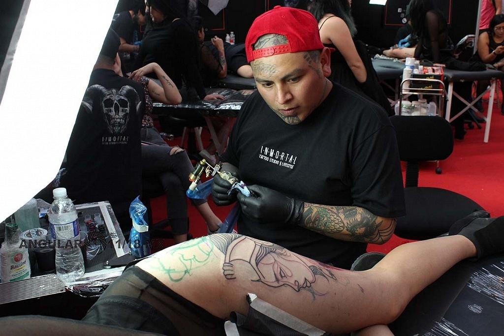 Expo Tattooarte México 2018 segunda edición, joven mujer realizándose un tatuaje en la pierna,