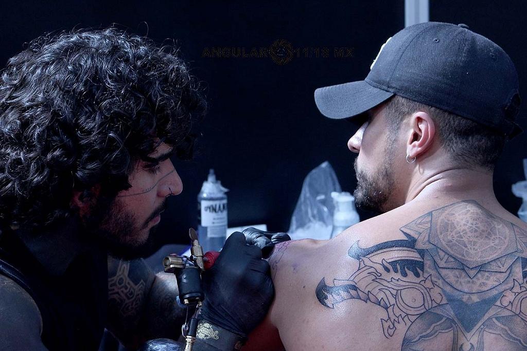 Expo Tattooarte México 2018, segunda edición, joven realizándose un tatuaje en la espalda